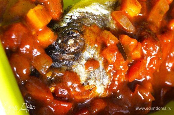Овощи переложить в форму для запекания, накрывая ими рыбу. Духовку разогреть до 170°С. Выпекать блюдо в течение 15 минут.