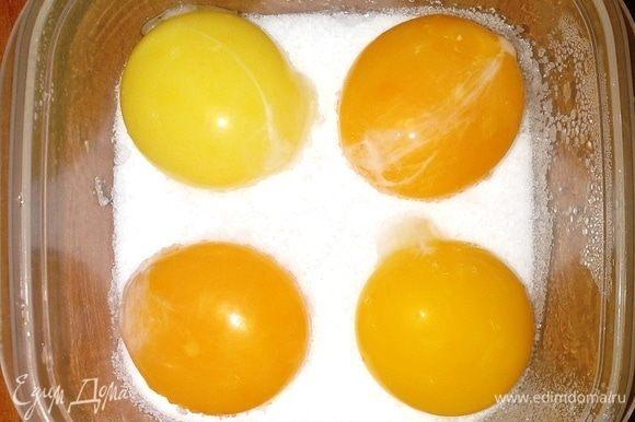 Засыпаем дно посуды слоем смеси из соли и сахара. Контейнер выбираем из не окисляющегося материала. Аккуратно помещаем желтки в посуду на некотором расстоянии друг от друга. Затем полностью укрываем желтки смесью.