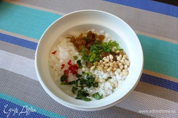 Смешаем рис, лук, изюм, кедровые орехи, мяту и петрушку. Добавим по вкусу соль и перец чили. Перемешаем.