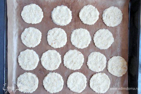 Влажными руками аккуратно расплющить каждый шарик теста в круг диаметром 5-6 см. Посыпать кунжутом. Выпекать 35 мин., пока крекеры не подсохнут и не станут слегка коричневыми.