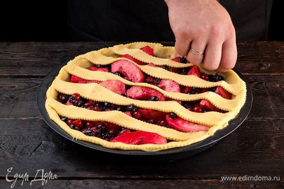 Возьмите еще часть теста, тонко раскатайте и нарежьте полосками шириной 1 см. Выложите полоски теста на пирог. Также по желанию можно вырезать из теста декоративные украшения для пирога. Оставьте пирог на 30 минут подняться.
