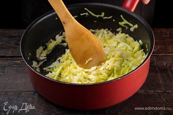 Приготовьте начинку. Для этого капусту нашинкуйте тонкой соломкой и выложите в сковороду. Добавьте немного воды и тушите до выпаривания жидкости.