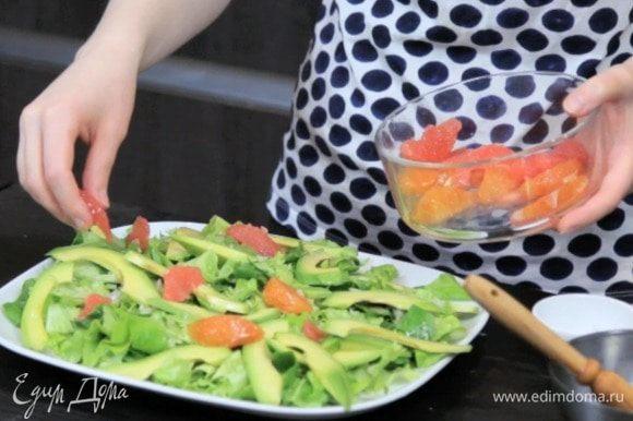 Собрать салат: выложить на блюдо подушку из салатных листьев, посыпать луком, добавить дольки авокадо и цитрусовых.