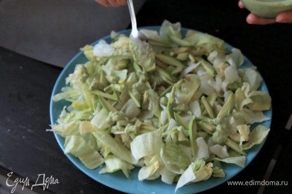 На тарелку выложить подушку из салатных листьев, сверху — авокадо и добавить часть заправки.