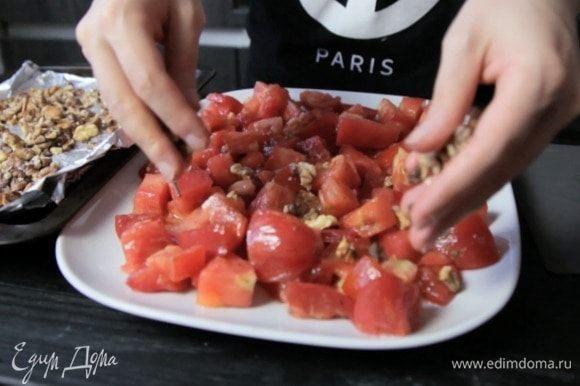 Заправить томаты, выложить на блюдо, посыпать орехами.