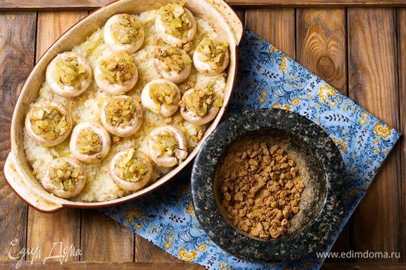 Смазать керамическую или стеклянную форму для запекания оставшимся растительным маслом и выложить рис ровным слоем. На рис положить шляпки шампиньонов и наполнить их жареным с грибами луком. Посыпать раскрошенными хрустящими бородинскими отрубями «Лито». Запекать 15 минут в духовке, нагретой до 200°С.