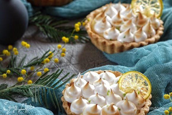 Украсить готовые тарталетки ломтиками лаймов, посыпать цедрой лимона и подавать.