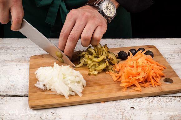 Нарежьте полукольцами репчатый лук и натрите на терке морковь. Соленый огурец нарежьте кубиками, а маслины без косточек — колечками.