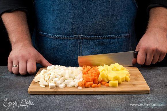 Картофель и лук очистите, нарежьте кубиками, морковь и корень сельдерея также нарежьте. В сковороду налейте оливковое масло и припустите лук, морковь, сельдерей.