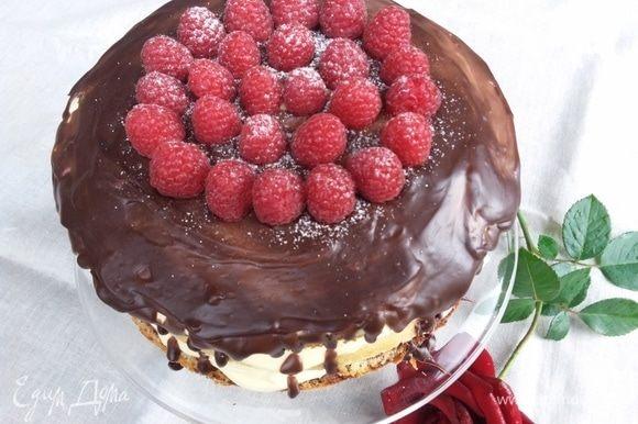 Украсить торт оставшейся малиной и посыпать сахарной пудрой.