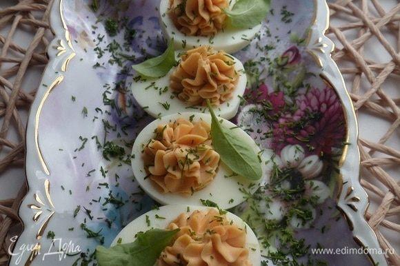 Выкладываем фаршированные яйца на блюдо. Посыпаем нарезанной зеленью.
