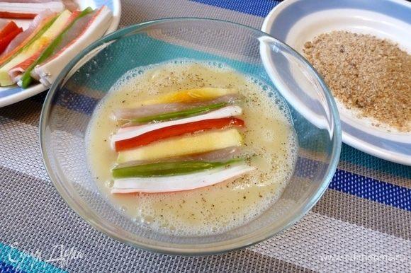 Обмакиваем подготовленную закуску в яйцо, а затем в сухари.