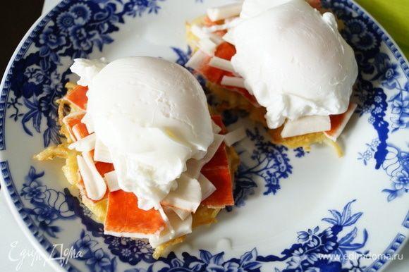 На готовые картофельные «блинчики» выложить порезанные крабовые палочки (количество по желанию, у меня ушло по 1 шт. на порцию). Поверх поместить подготовленные яйца-пашот.