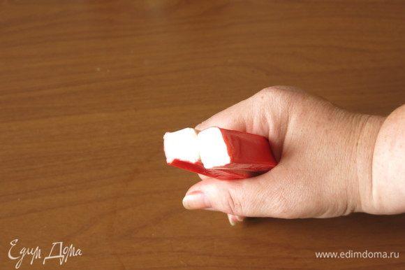 С крабовых палочек снимаем пленку и объединяем по две, белой стороной друг к другу.
