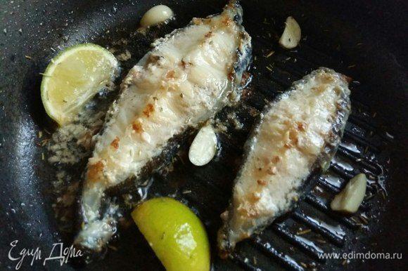 Перевернуть рыбку и выложить в сковороду чеснок, дольки лайма, посыпать розмарином и травками (щепотку), чтобы слегка оттенить вкус рыбы пряностью. Кому не нравится вкус пряных трав, можно и без трав обойтись легко. И жарим еще минут 5.