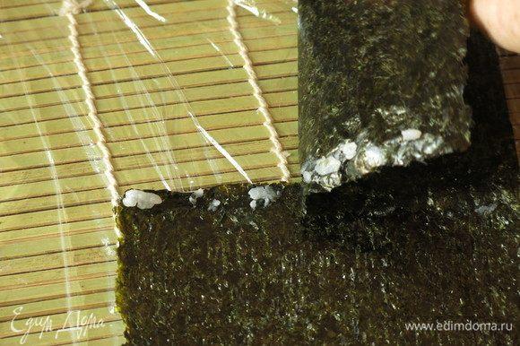 Сборка кадзари — еще разрезаем 2 нори по длине палочек. Две полоски нори соединяем, но уже не водой, а рисинками, для прочности — раскладываем рисинки по краю, кладем лист сверху и прижимаем.
