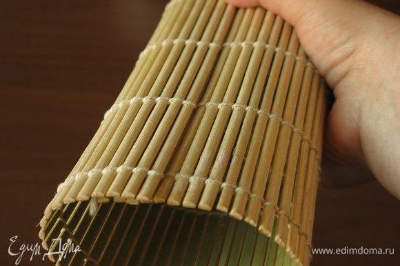 Прижимаем суши ковриком не меняя расположения, снизу придерживаем ладонью.