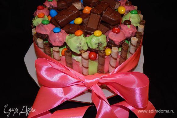 Украшаем торт конфетами и вафельными трубочками. Из обрезков коржей я сделала кейк боллы. Бисквит измельчить в блендере, добавить крем, чтобы получилась пластичная масса. Скатать шарики и обмазать их кремом.