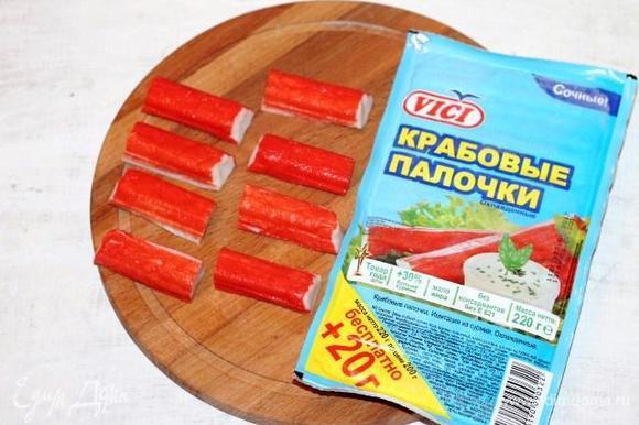 Берем из упаковки 4 крабовые палочки и разрезаем каждую пополам.