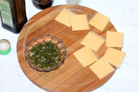 Каждую пластину сыра разрезаем на 4 части. Приготовим соус для баклажан. Измельченный укроп (зелень) перетираем с солью и прессованным чесноком. Добавляем бальзамический уксус и оливковое масло, перемешиваем. Если соус слишком густой, можно добавить 1 ч. л. воды.