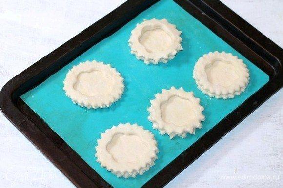 Перекладываем заготовки на противень, застеленный заранее силиконовым ковриком. Отправляем противень в духовку. Включаем минимальную температуру духовки от 40–100°C и оставляем волованы до увеличения в 2 раза.