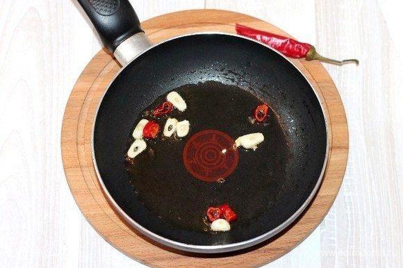 На разогретом растительном масле (2 ст. л.) обжариваем кусочки острого перца и порезанный слайдами чеснок до появления аромата. Овощи со сковороды удаляем, масло оставляем.