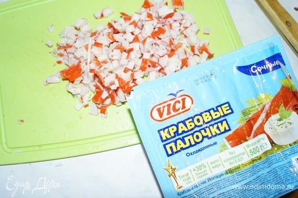 Тем временем, пока готовится корж, приготовим салат. Для этого отварим до готовности рис. Крабовые палочки ТМ VICI мелко нарежем.