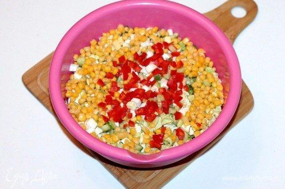Выкладываем порезанные продукты в большую миску. Добавляем кукурузу без жидкости, сладкий перец (0,5 шт.), порезанный кубиками, и укроп (1/2 часть), перемешиваем.