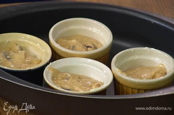 Небольшие керамические формочки смазать сливочным маслом и заполнить тестом чуть больше чем на половину.