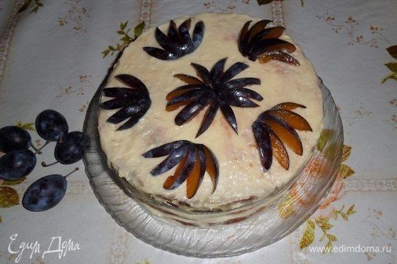 Охлажденный торт украшаем нарезанными сливами.
