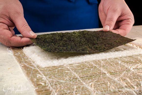 Смочив руки в смеси тэдзу, возьмите коврик положите сверху рис и разровняйте, образуя прямоугольник. Сверху положите нори.
