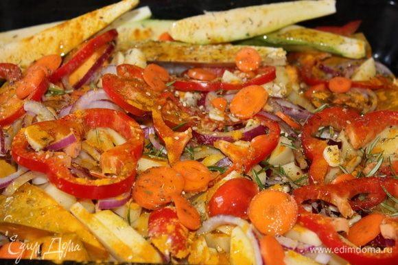 Тем временем подготовить, желательно, глубокий противень. Очистить картофель, лук, чеснок, тыкву, морковь. В противень картофель порезать крупными, но не очень толстыми дольками. Лук порезать полукольцами. Чеснок порезать мелко. Тыкву порезать крупными кусками. Морковь нарезать тонкими кругляшами. Кабачок разрезать вдоль на несколько длинных треугольных долек. Болгарский перец помыть, отрезать половину, убрать семена, если есть, и нарезать тонкими кругляшами, не более 5-6 мм. Добавить листья свежего розмарина, куркуму, соль, тимьян, посыпать смесью свежемолотого перца, кунжутными семенами, тростниковым сахаром, натереть мускатный орех.