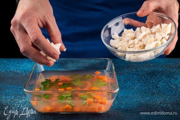 В форму налейте тонким слоем бульон и дайте ему застыть. Затем выложите морковь, зелень. Сверху положите кусочки рыбы и залейте все бульоном до краев. Поставьте формочки в холодильник на несколько часов до полного застывания. Лимон нарежьте тонкими ломтиками, используйте также оставшуюся зелень.