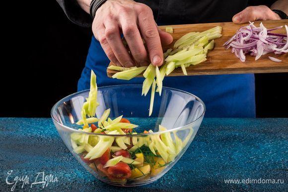 У сладкого перца снять кожицу и удалить семена, мякоть тонко порезать и выложить в салат. С огурцов снять кожуру и тонко их нарезать. Красный лук почистить и нарезать тонкой соломкой. Добавить в салат.