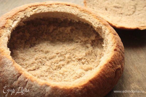 Для подачи вам понадобится круглая буханка хлеба: ищите среднего размера, чтобы она вместила в себя не больше одной порции супа. Срежьте верхний слой буханки, это будет наша крышечка. Аккуратно удалите часть хлебного мякиша, оставив при этом толстые стенки и толстое дно (иначе хлеб впитает суп и размякнет, потеряв форму). Отправьте хлеб в духовку, разогретую до 250°С, на 5-7 минут, чтобы он лучше схватился.