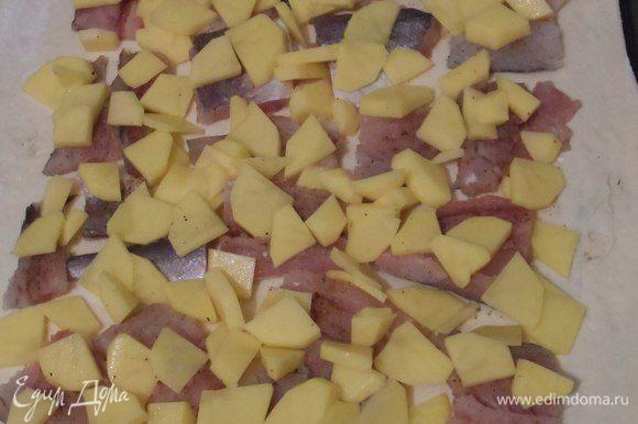 Картофель очищаем, нарезаем небольшими ломтиками. Раскладываем на рыбу и заполняем промежутки. Немного солим.