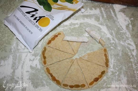 Разделить вырезанный круг на 8 частей. По краю выложить изюм (по желанию можно заменить орехами). Завернуть к середине (см. фото).