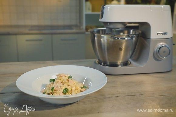 Выложите готовые тальятелле на тарелки, полейте сливочным соусом и украсьте лепестками петрушки.
