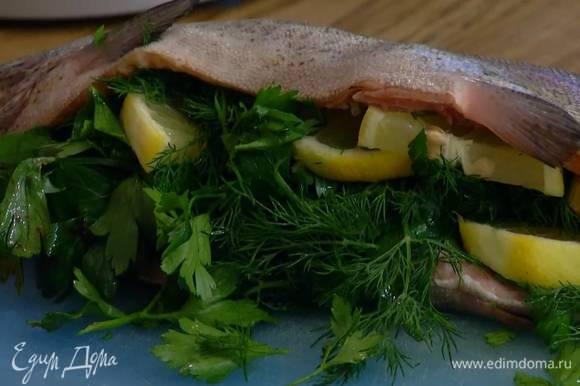 В брюшко форели поместить листья петрушки, укропа и нарезанный лимон.