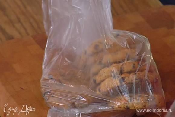 Печенье поместить в полиэтиленовый пакет и измельчить скалкой в мелкую крошку, затем всыпать его в растопленное сливочное масло и все перемешать.
