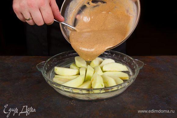 Форму для выпечки смажьте сливочным маслом. Выложите нарезанные яблоки ровным слоем и залейте равномерно тестом.