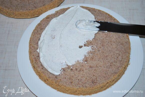 Остывший бисквит разрежем на две части. Нанесем часть крема.