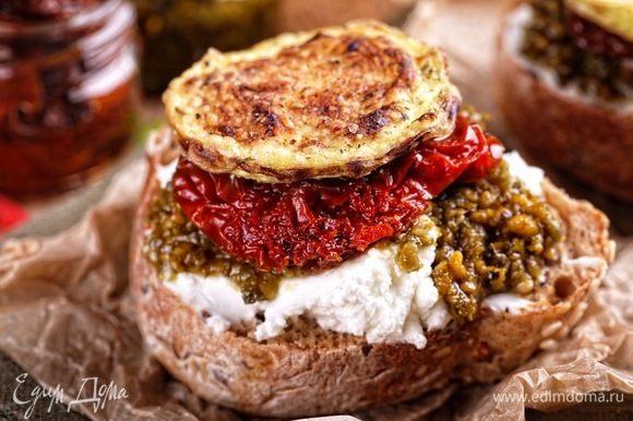Остается только подключить фантазию и собрать вот такой маленький бутербродик: ломтики багета смазать оливковым маслом и подсушить на сухой сковороде, сверху выложить по 1 ст. л. творожного сыра, на него — ломтик вяленого помидора, на него — столовую ложку свежего песто (у меня покупной) и закончить эту башенку ломтиком хрустящего кабачка! Подавать немедленно к вину или просто так:) Это очень вкусно!