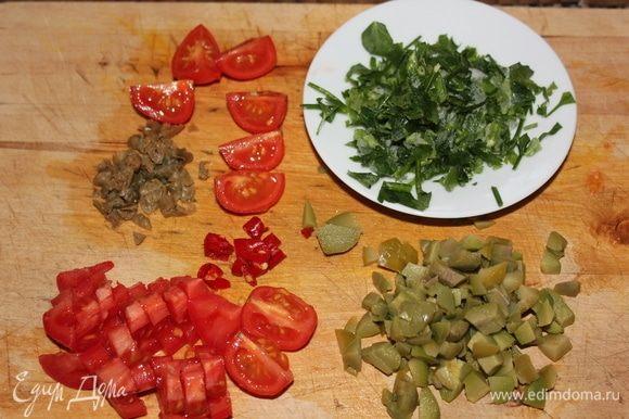 Как закипела вода, закинуть в кастрюлю спагетти и варить 9,5 минут. Тем временем подготовим каперсы, промытые под проточной водой от соли. Мелко нарезать каперсы, пеперончино, свежую петрушку (у меня была свежемороженая), оливы и помидоры черри. Черри достаточно разрезать на 4 части.