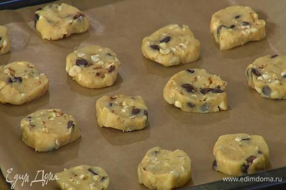 В тесто добавить орехи и шоколад, сформировать из теста поленце, нарезать кружками толщиной в 1 см и выложить их на противень, выстеленный бумагой для выпечки.
