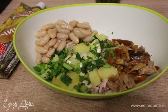 Добавить консервированную фасоль и мелко нарезанные зеленый лук и петрушку.