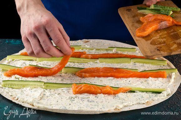 Выложите полоски нарезанной семги и огурца.