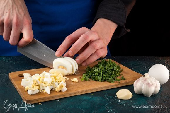 Отварите яйца и порубите кубиками. Нашинкуйте зелень и измельчите чеснок.
