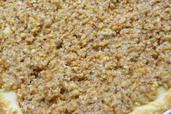 Достать подрумяненное тесто, удалить бумагу с фасолью и выложить на тесто ореховую начинку.