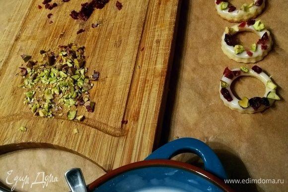 Теперь можно заняться творчеством и украшательством. Из лимонного сока и сахарной пудры смешать помадку. Нарубить фисташки и вяленую или сушеную вишню или клюкву. Колечки обмакнуть в помадку и посыпать орешками и фруктами. Дать подсохнуть.
